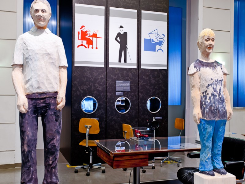 ": Wooden figures are standing on the listening stations in the exhibition ""At Work"" on level 3."