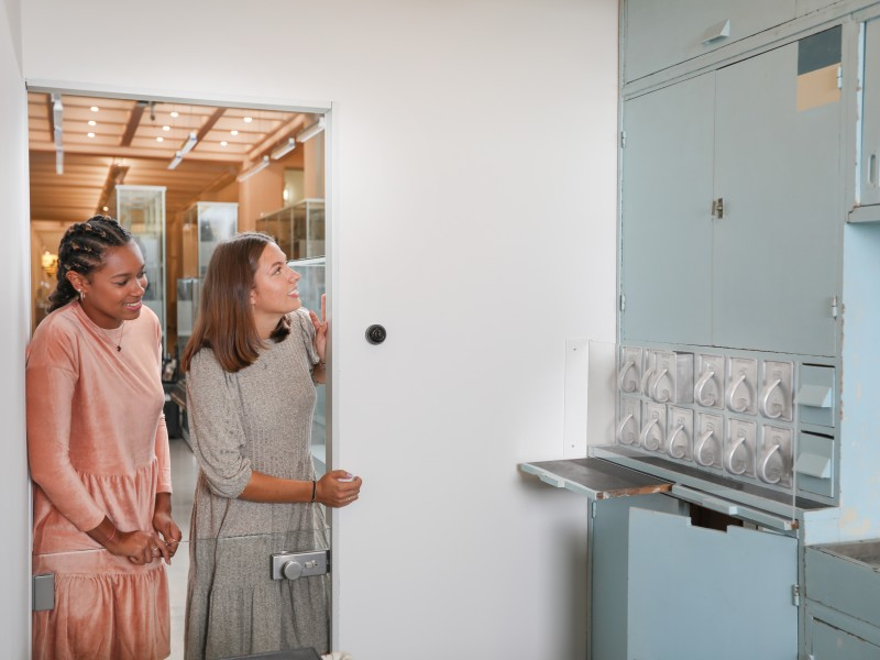 "Two girls take a look at the model of a ""Frankfurt Kitchen"" in the ""Everyday Life"" exhibition."