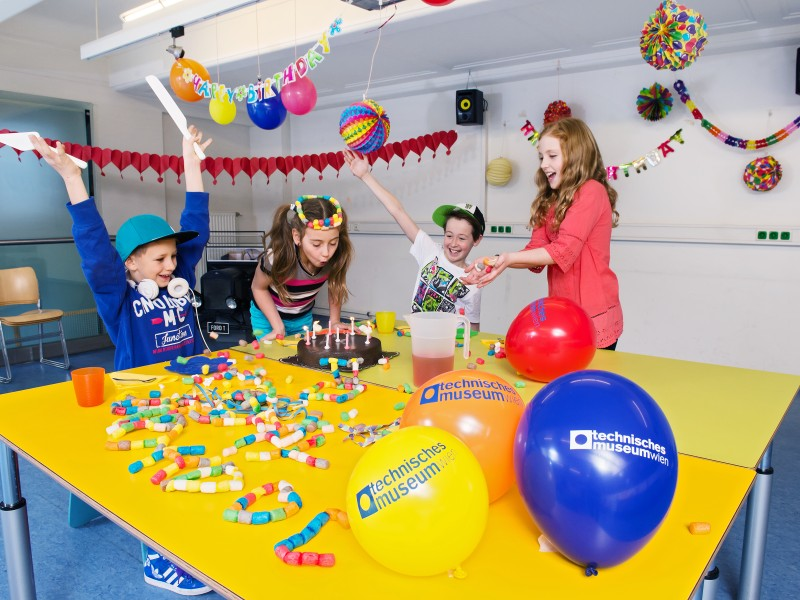 Children are celebrating a birthdayparty in the partyroom with a lot of decoration and a cake
