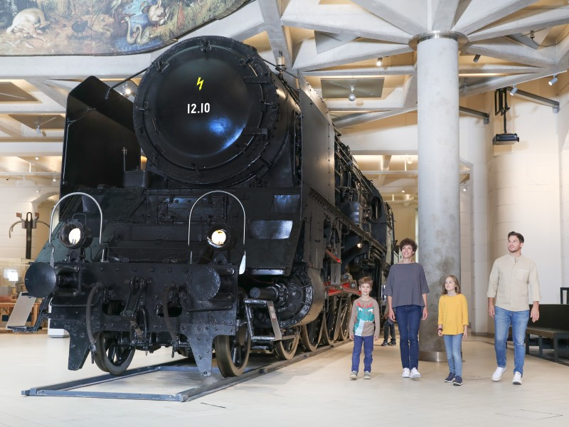": A family visits together the Exhibition ""12.10 A Superlative Steam locomotive"" and takes a look at the locomotive."