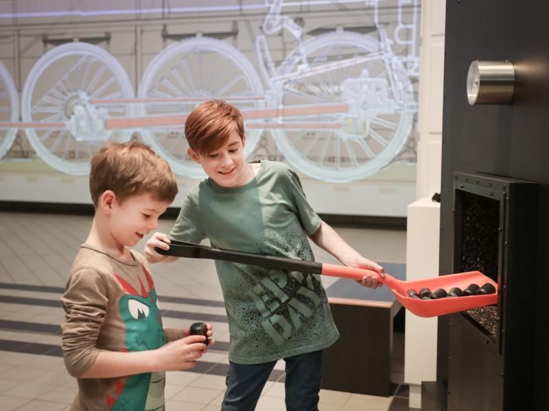 "One child shovels coal into the kettle, another holds a lump of coal in his hands. A hands-on object from the exhibition ""12.10 a Superlative Steam locomotive"""
