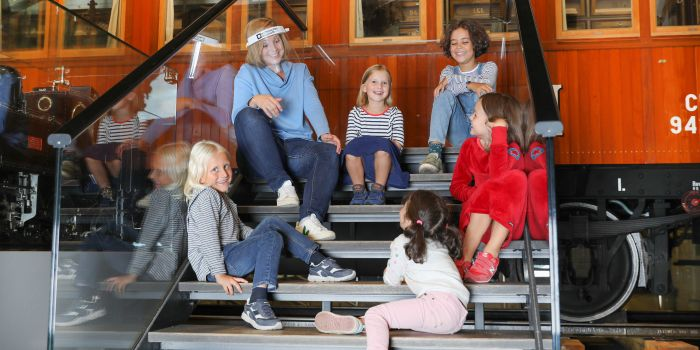 ": Children sit together with a tour guide on the stairs from Sisi´s Hofsalonwagen. It is part of the exhibition ""Lok.Erlebnis"""