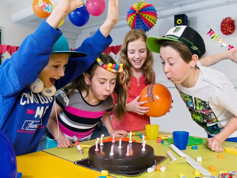 : Children are celebrating a birthdayparty in the partyroom with a lot of decoration and a cake