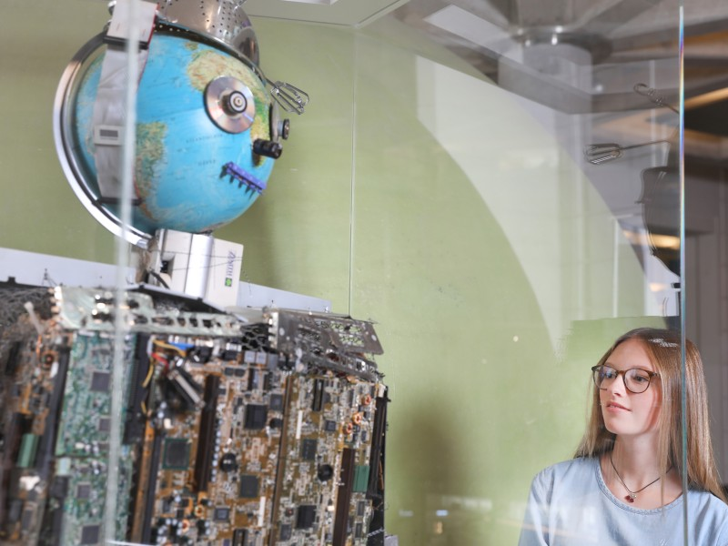 "Teenager looks at the humanoid robot ""Schrotty Bob"" in the exhibition ""Everyday Life"""