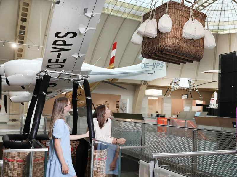 "Two teenagers are standing in a hot air balloon basket which is movable as soon as you step on it. Part of the exhibition ""Mobility"""