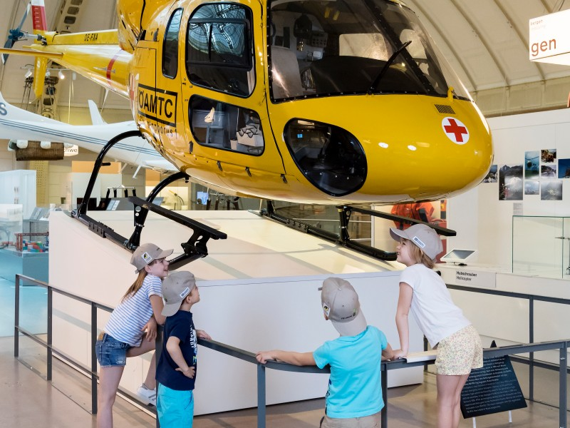 ": Children from the ""Technik und Tiere"" Summercamp are looking at the helicopter in the exhibition ""Mobility"" on level 4."