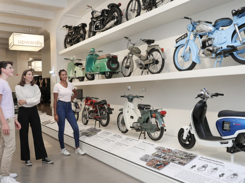 "A small group of teenagers look at various mopeds and motorcycles in the exhibition ""Mobility""."